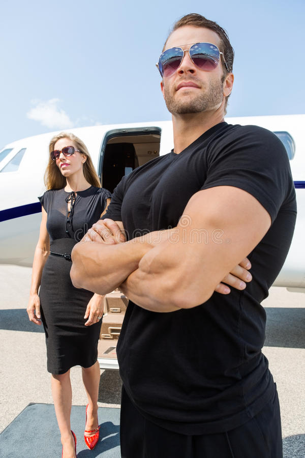 Bodyguard Standing Against Woman And Private Jet. Bodyguard with arms crossed standing against women and private jet stock image