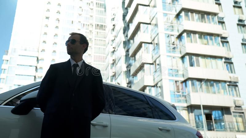 Bodyguard standing near business car, checking safety and security, bottom view royalty free stock photography