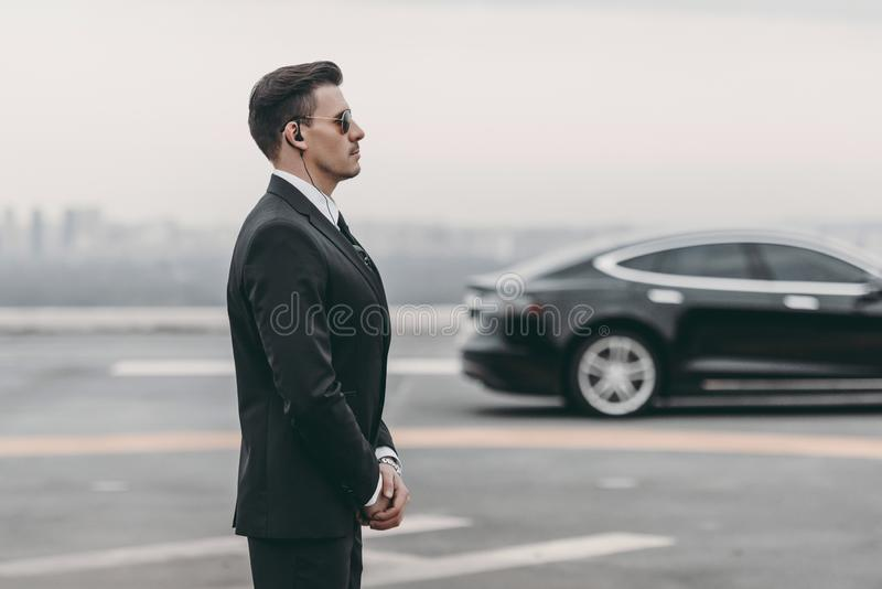 Bodyguard in suit with security earpiece standing close to. Politician car royalty free stock photos