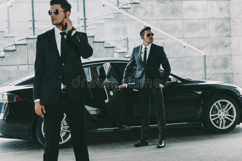 Bodyguards in sunglasses standing at car and waiting. For politician royalty free stock photos