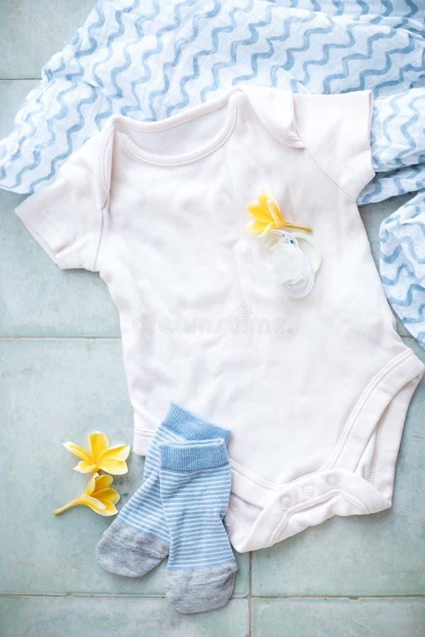 Bodysuit, манекен, носки и пеленка ребенка Младенческие одежды на светлой предпосылке стоковая фотография rf