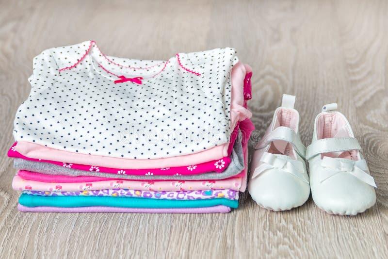 Bodysuit cor-de-rosa e branco dobrado com as sapatas nele fundo de madeira cinzento tecido para a menina recém-nascida Pilha de r imagem de stock