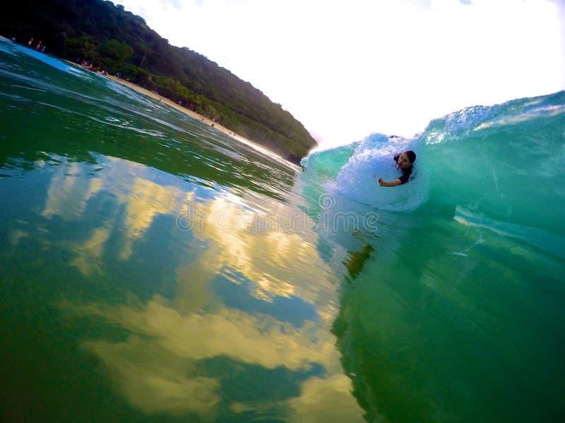 Bodysurfing Waimea Bay. A girl in the barrel at Waimea Bay Hawaii stock photos