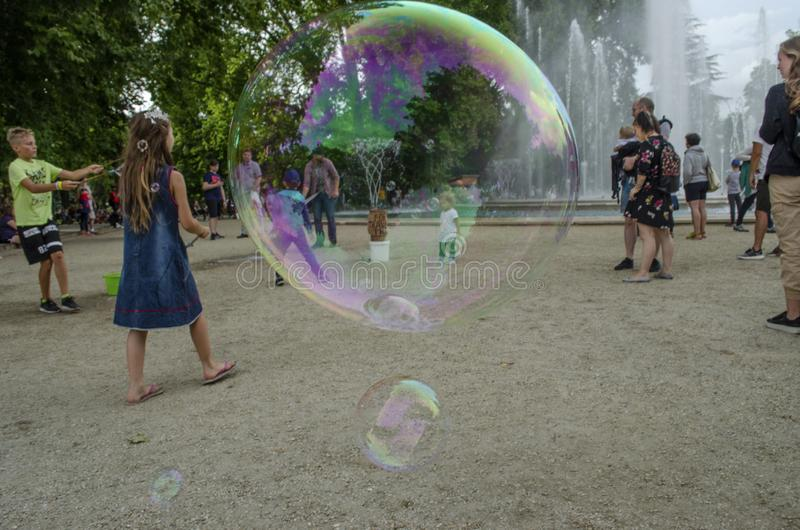 Boedapest, Hongarije - 13 Juli, 2019 jonge geitjes geniet water van fontein met kleurrijke zeepbel met familieleden tijdens royalty-vrije stock foto's