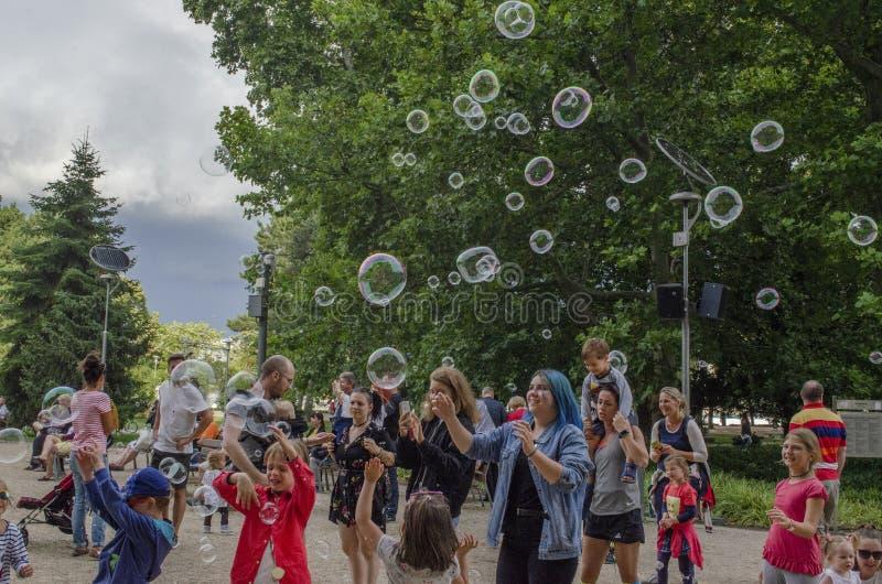 Boedapest, Hongarije - 13 Juli, 2019 Jonge kinderen speelt met kleurrijke zeepbel in een openluchtpark met familie tijdens royalty-vrije stock fotografie