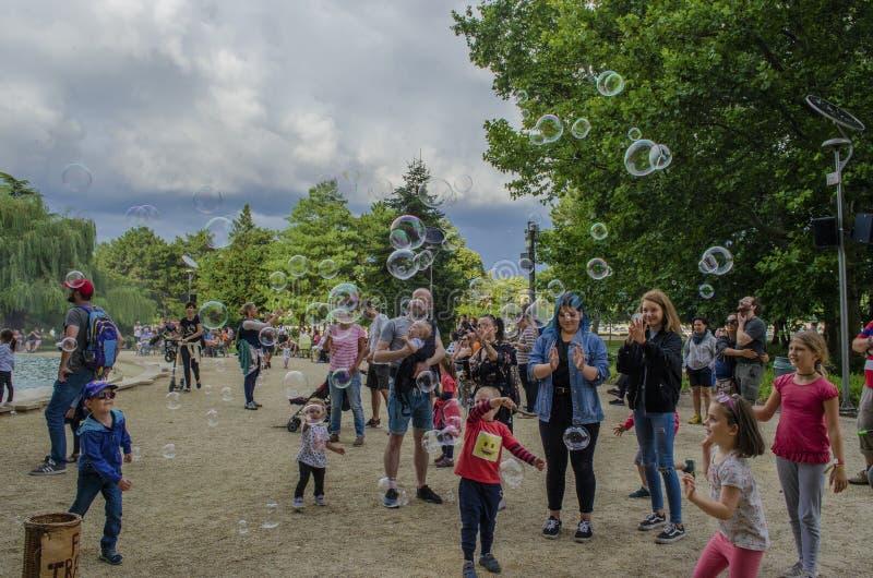 Boedapest, Hongarije - 13 Juli, 2019 Jonge kinderen speelt met kleurrijke zeepbel met familieleden tijdens de zomer royalty-vrije stock fotografie