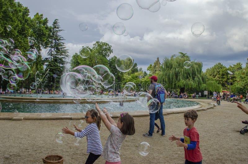Boedapest, Hongarije - 13 Juli, 2019 Jonge kinderen speelt met zeepbel in een openluchtpark met familie tijdens de zomer stock afbeelding
