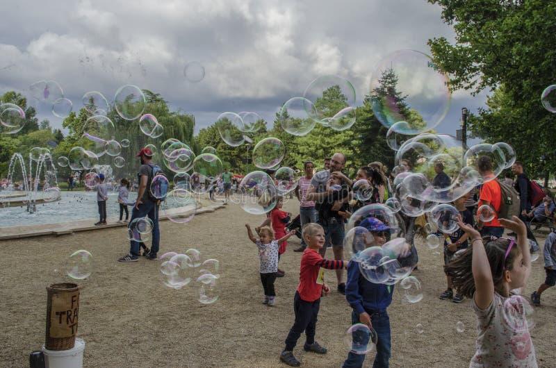 Boedapest, Hongarije - 13 Juli, 2019 Jonge kinderen speelt voor waterfontein met kleurrijke zeepbel met familie royalty-vrije stock afbeeldingen