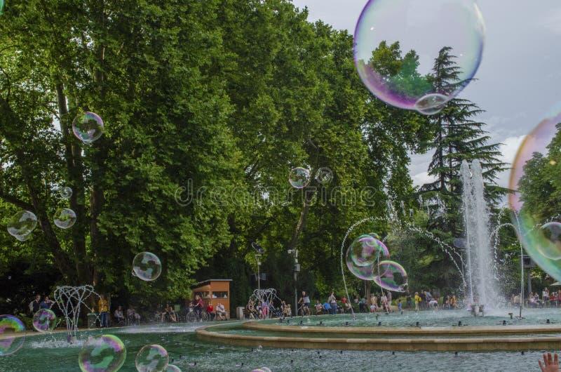 Boedapest, Hongarije - 13 Juli, 2019 Mensen geniet water van fontein met kleurrijke zeepbel met familieleden tijdens stock afbeelding