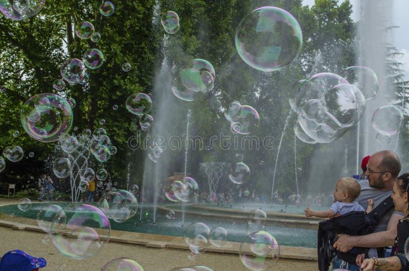 Boedapest, Hongarije - 13 Juli, youndjong geitje van 2019 A geniet water van fontein met kleurrijke zeepbel met familieleden royalty-vrije stock fotografie