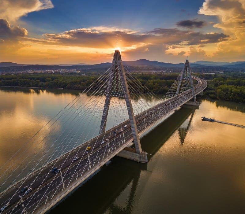 Boedapest, Hongarije - Megyeri-Brug bij zonsondergang met motorboot op Rivier Donau en zwaar verkeer stock afbeeldingen