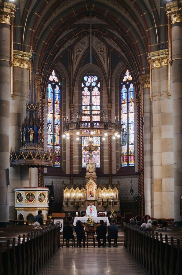 BOEDAPEST, HONGARIJE - SEPTEMBER 18, 2016: Parochianen en priester in kerk van St Elizabeth van het Huis van à  rpà ¡ D Het binn stock foto