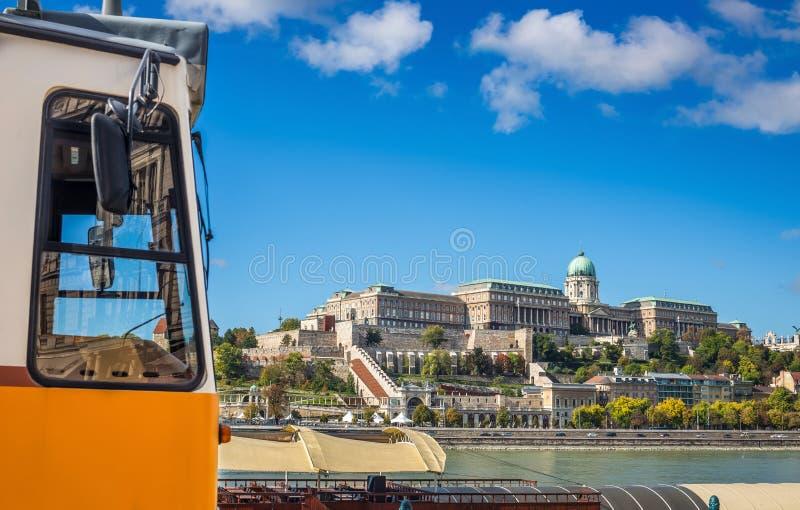 Boedapest, Hongarije - Traditionele gele Hongaarse tram bij de rivieroever van Donau met Buda Castle Royal Palace royalty-vrije stock afbeelding
