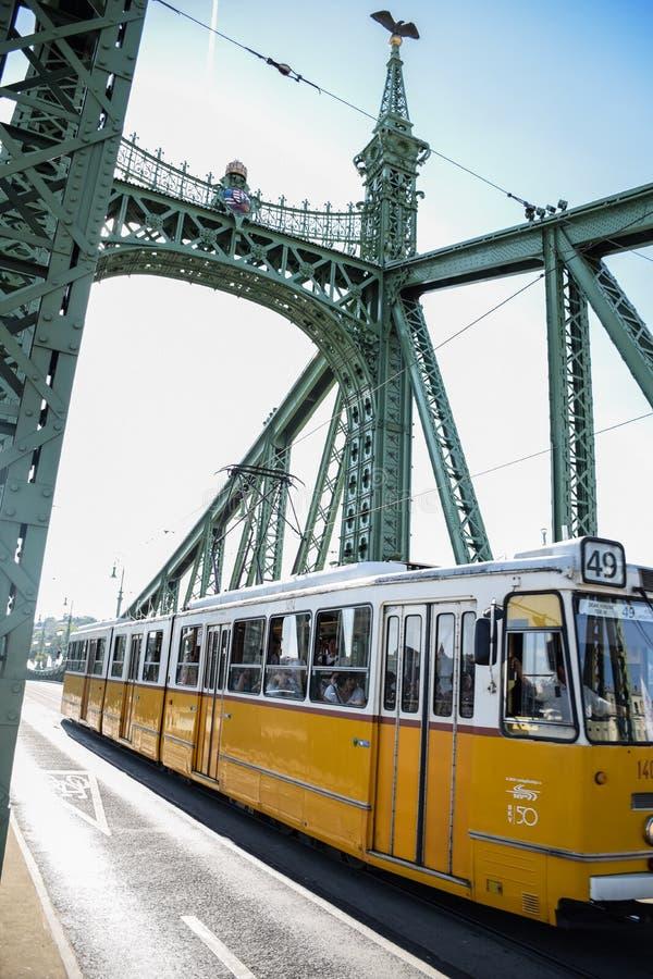 Boedapest, Hungagry - september, 12, 2018 - Gele Tram kruist vrijheidsbrug royalty-vrije stock fotografie