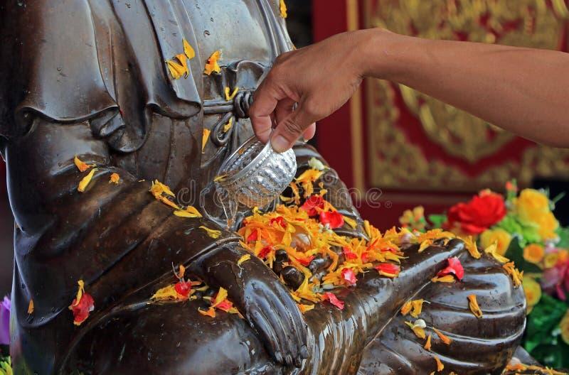 Boeddhistisch giet water op het standbeeld van Boedha royalty-vrije stock afbeelding