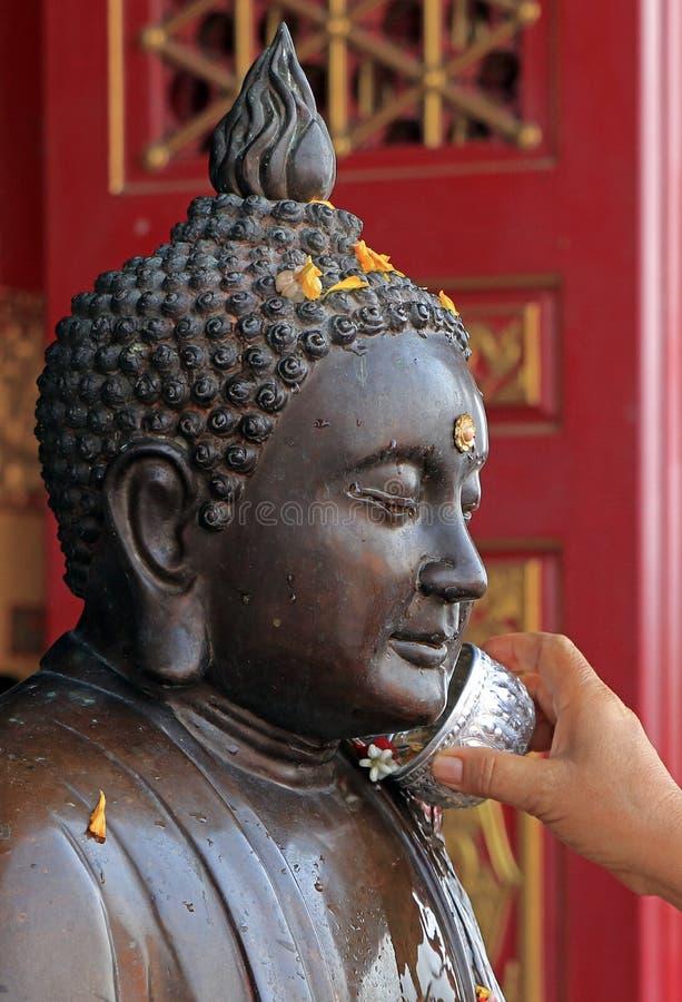 Boeddhistisch giet water op het standbeeld van Boedha royalty-vrije stock fotografie