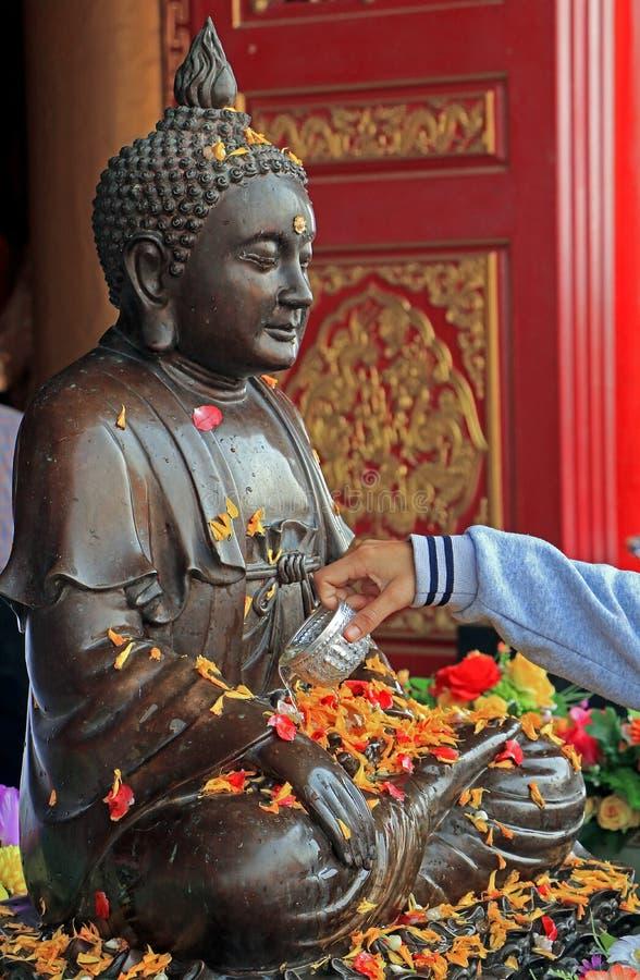 Boeddhistisch giet water op het standbeeld van Boedha stock foto's