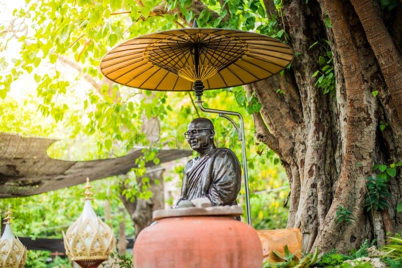Boeddhistisch standbeeld die onder grote boom mediteren royalty-vrije stock foto