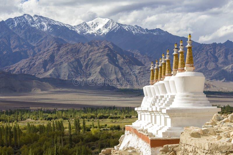 Boeddhistische chortens, de witte stupa en bergen van Himalayagebergte op de achtergrond dichtbij Shey-Paleis in Ladakh, India stock afbeelding
