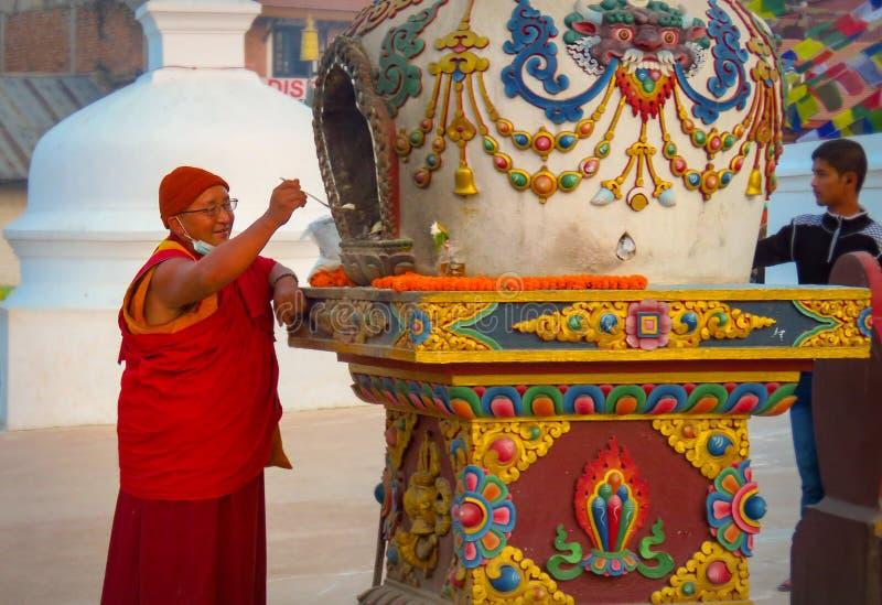 Boeddhistische monnik die aanbiedingen maakt bij Boudhanath-stupa stock foto