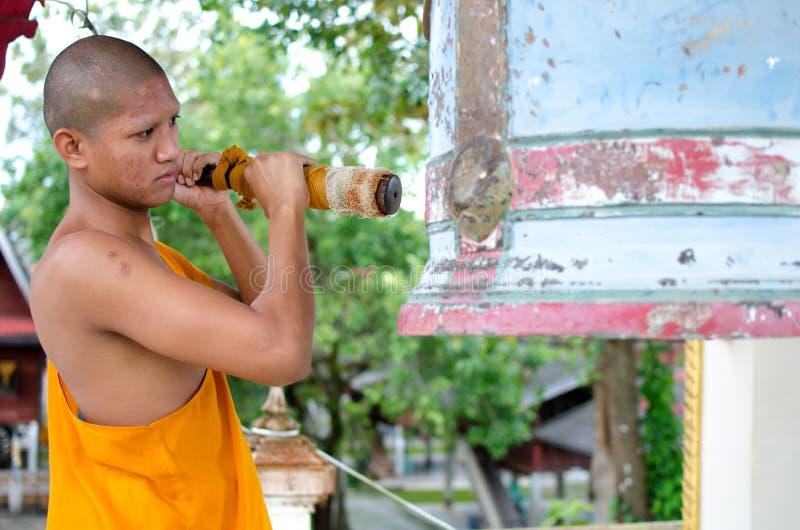 Boeddhistische monnik, die de Klok in de tempel raken. royalty-vrije stock fotografie