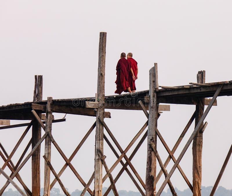Boeddhistische monniken die op de brug in Myanmar lopen stock foto