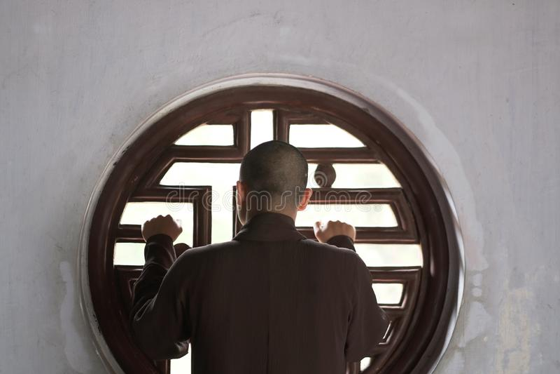 Boeddhistische monnikstribunes door een rond venster royalty-vrije stock afbeeldingen
