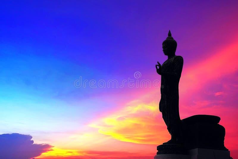 Boedha die zich achter de de Menings Trillende Overzeese zonsondergang van het Achtergrond Roodbruine Oranje Hemelplan Stedelijke royalty-vrije stock fotografie