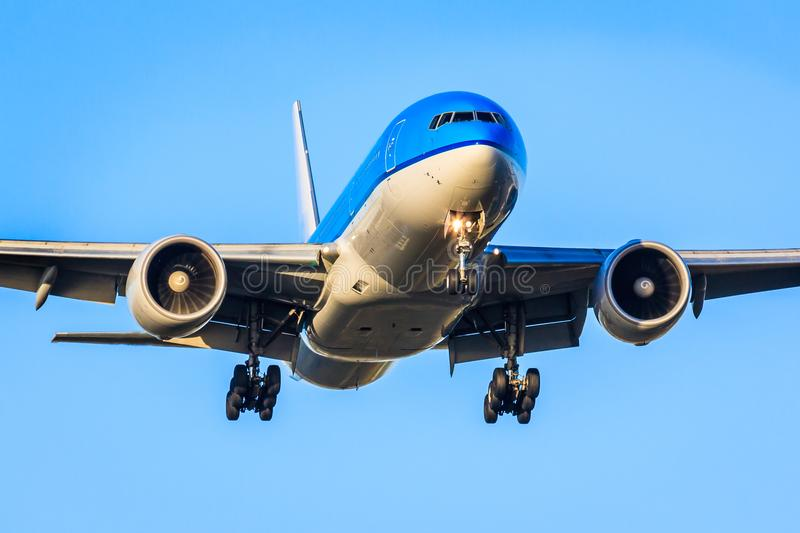 Airliner approaching to land. Boeing 777 approaching to land, front view, blue sky, gear down royalty free stock image