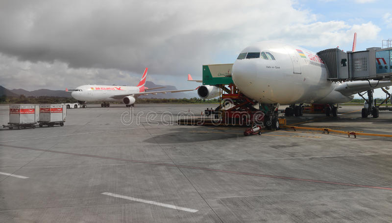 The Boeing B777 300/200 LR Air Mauritius. Maintainance unit preparing Boeing B777 300/200 LR Air Mauritius for flight on SSR International Airport,Mauritius stock photography
