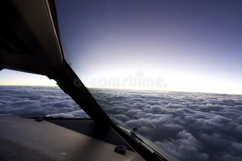 Inside Cockpit of aeroplane over the sky. Aeroplane fly over cloudy sky in the evening. Seen from inside cockpit while pilot operating the flight stock images