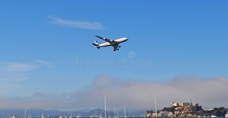 Boeing 747 flyger på en låg höjd över den Alcatraz ön arkivfoto