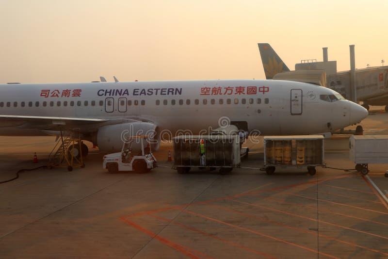 Boeing 737-800 flygplan, nivån av Kina östligt ladda bagage på förklädet på Phnom Penh den internationella flygplatsen royaltyfri fotografi
