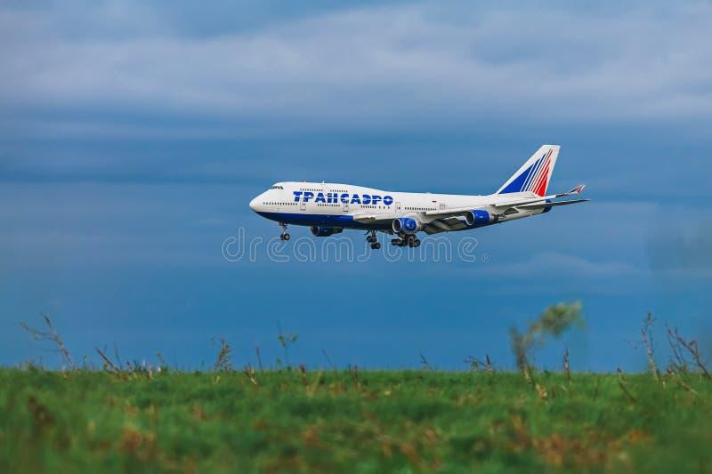 Boeing 747-400 Transaero flygbolag på bakgrunden av stormmoln royaltyfri foto