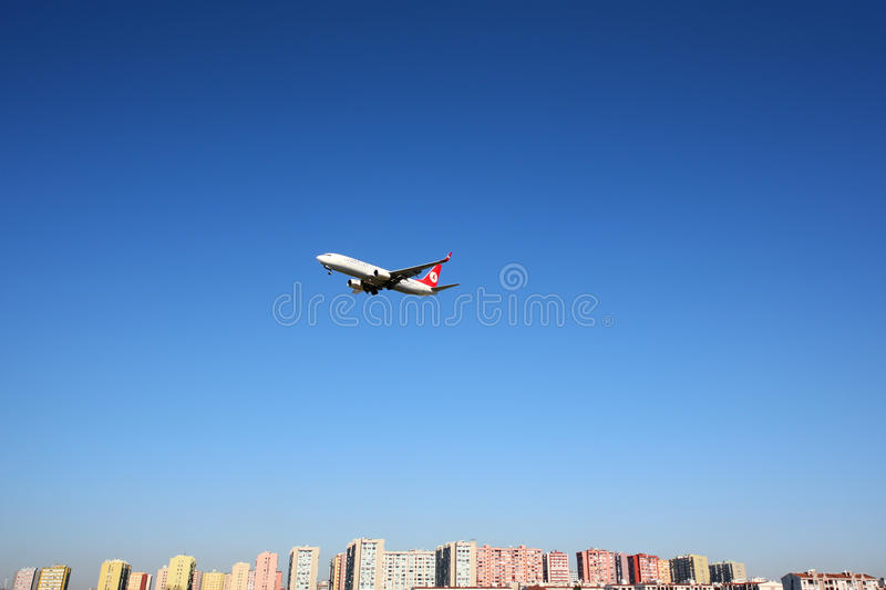 Boeing 737-800 of Turkish Airlines shown over Istanbul city, landing at Ataturk international airport. ISTANBUL, TURKEY - MARCH 19, 2014: Boeing 737-800 of royalty free stock photo