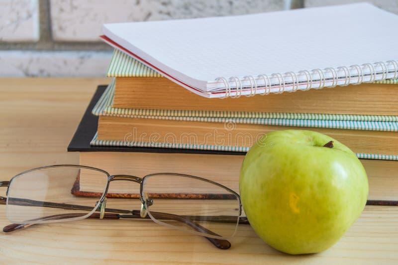 Boek, Apple, notitieboekje, lezend glazen en pen op houten lijst Terug naar het Concept van de School stock fotografie