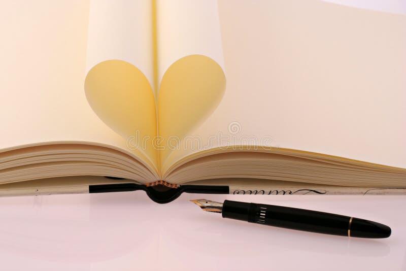 Boek met document zoals een hart en een vulpen stock afbeeldingen