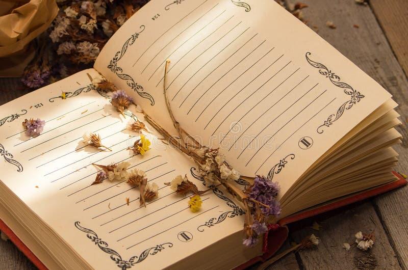 Boek om nota's met droge bloemen te schrijven stock afbeelding