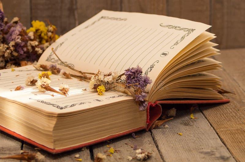 Boek om nota's met droge bloemen te schrijven stock afbeeldingen