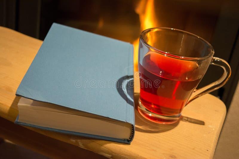 Boek, staatsgreep van thee en open haard stock afbeeldingen