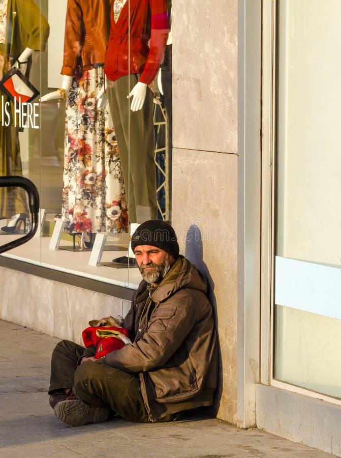 Boekarest, Roemenië, Februari 2016 - de Dakloze mens op de stoep dichtbij kleren winkelt royalty-vrije stock foto's
