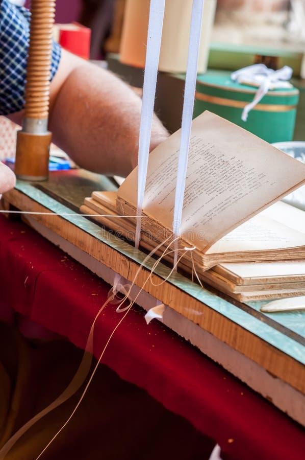 boekbinden Mannelijke arbeiders bindende pagina's royalty-vrije stock afbeelding