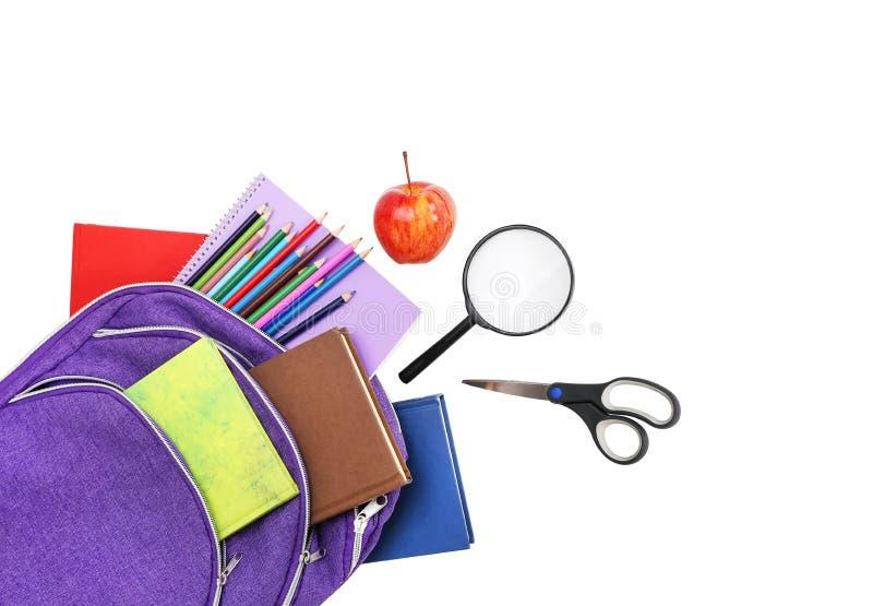 Boeken, appel, loupe, rugzak en potloden op wit stock fotografie