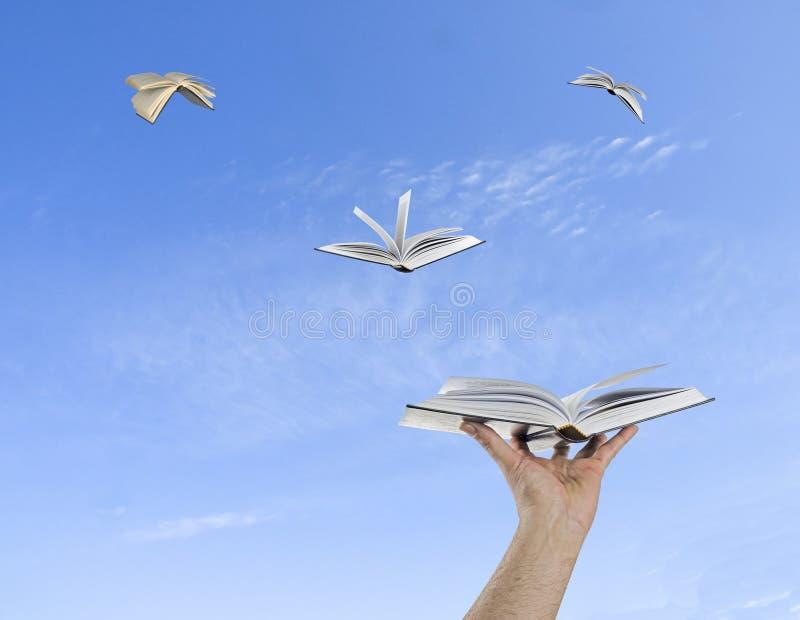 Boeken die van handen vliegen stock foto's