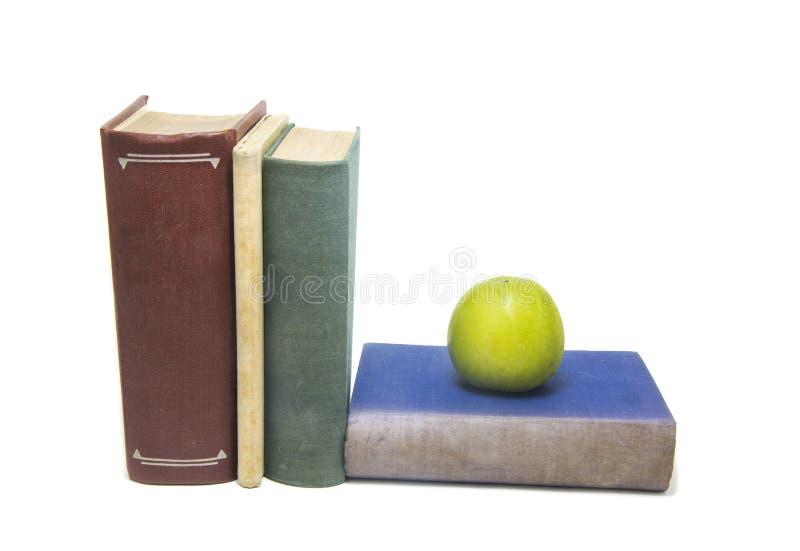 Boeken en groene appel die op witte achtergrond worden geïsoleerd royalty-vrije stock foto's