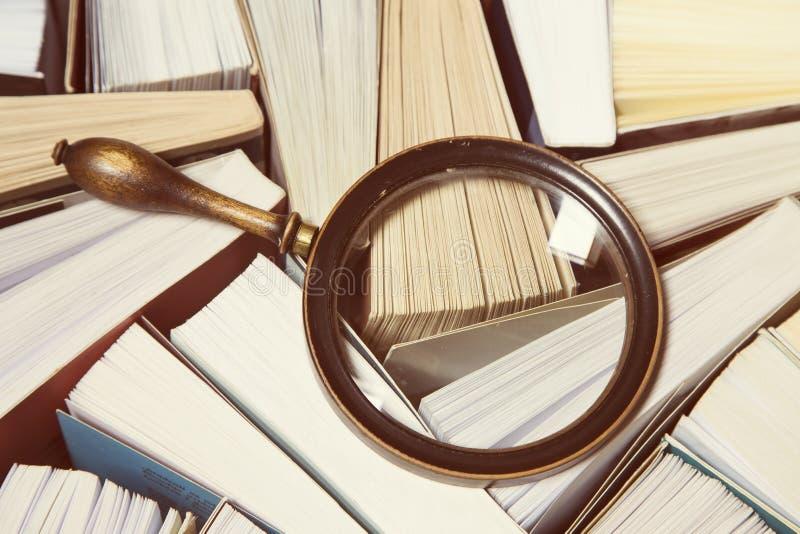 Boeken en het vergrootglas stock afbeeldingen