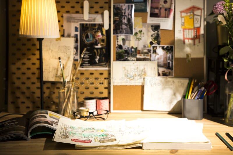 Boeken en ontwerpen op houten lijst onder lamplicht stock afbeeldingen