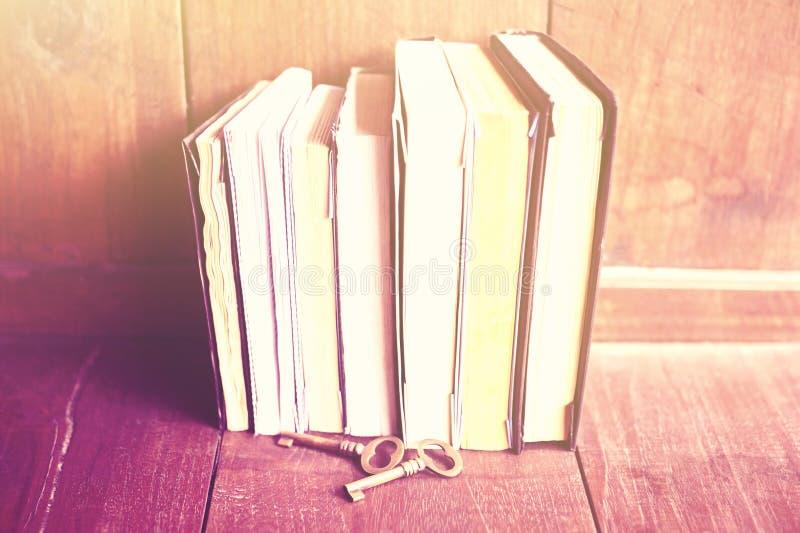 Boeken en sleutels op een houten vloer, uitstekend kleureneffect stock foto's