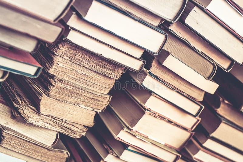 Boeken gestapelde achtergrond Stapels van oude boeken stock afbeeldingen