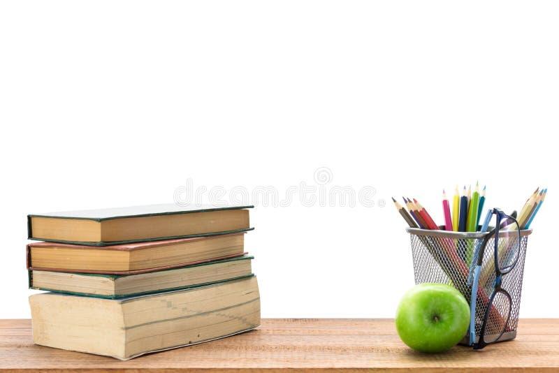 Boeken, kantoorbehoeften en een groene appel op het bureau stock afbeelding